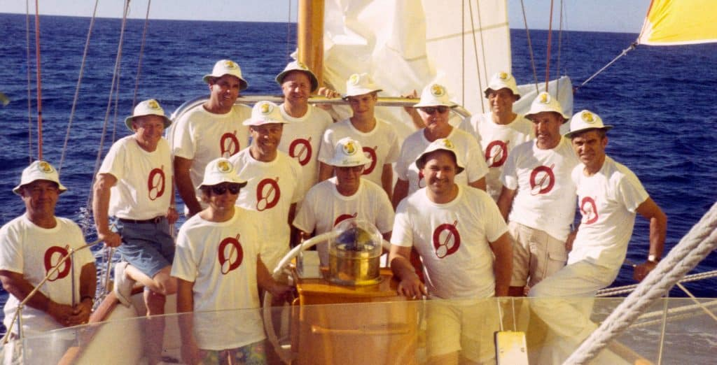 Crew of 15 in cockpit of large sailing yawl