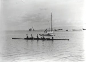 Racing shell in Honolulu Harbor with lighthouse in background.