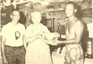 Mrs. Kamokila Campbell presents the Senior Men's Trophy to Dutchy Kino of Waikiki Surf Club in the 1950 Macfarlane Regatta as OCC President Ward Russell looks on.